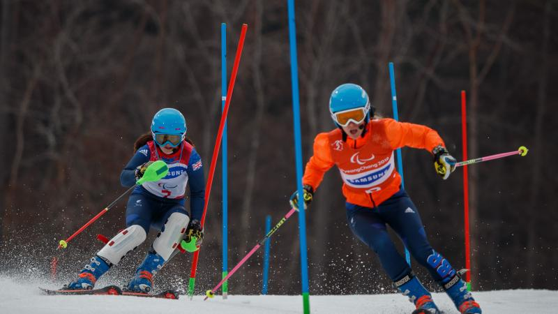 a female vision impaired skier and her guide go through the slalom gates