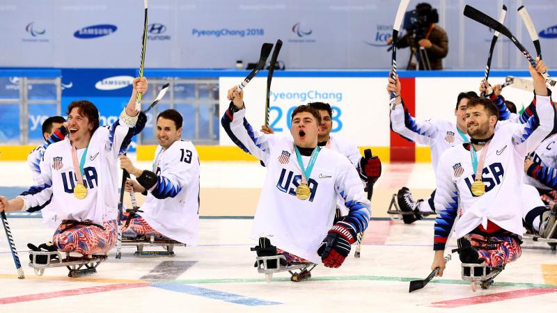 Para ice hockey players celebrating on the ice