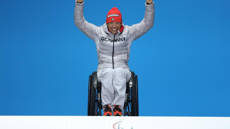 a wheelchair athlete raises her arms on the podium