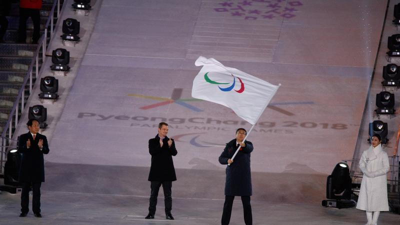 Three men standing, one of them holding a flag