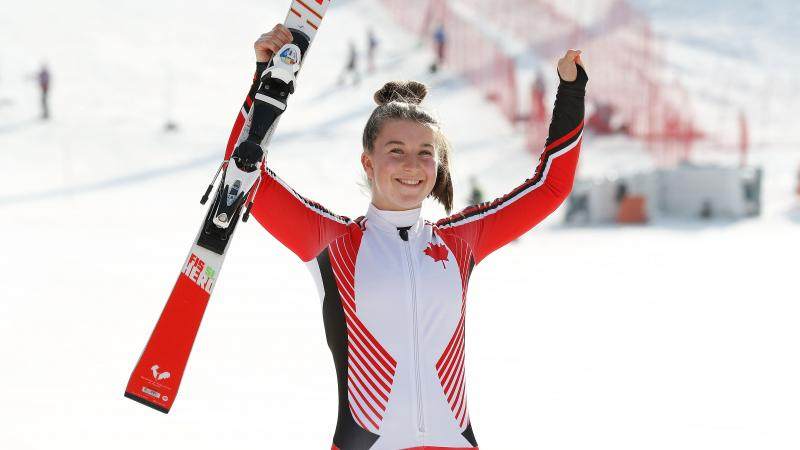 a female Para skier raises her arms in celebration