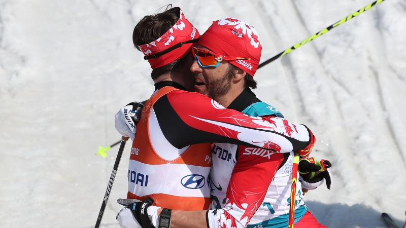 a visually impaired skier and his guide hug on the finish line