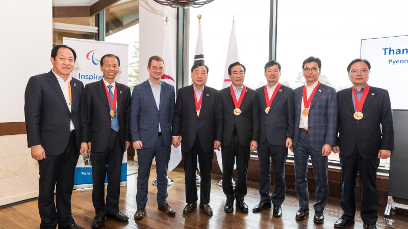 Eight men standing, six of them with the Paralympic Order medal