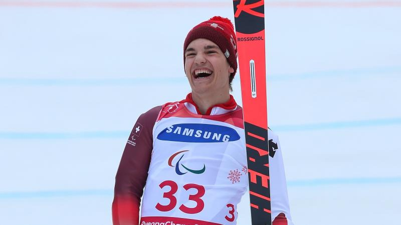 a male Para skier laughs in celebration