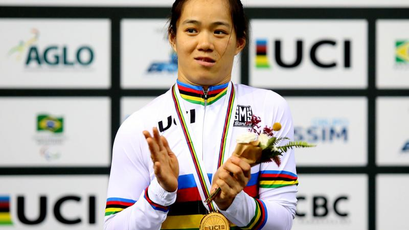 A female Para cyclist applauds on the podium