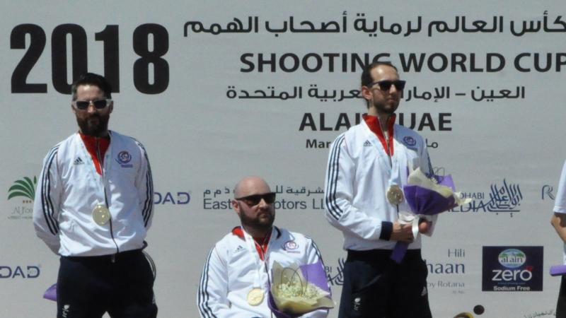 three male Para shooters on a podium