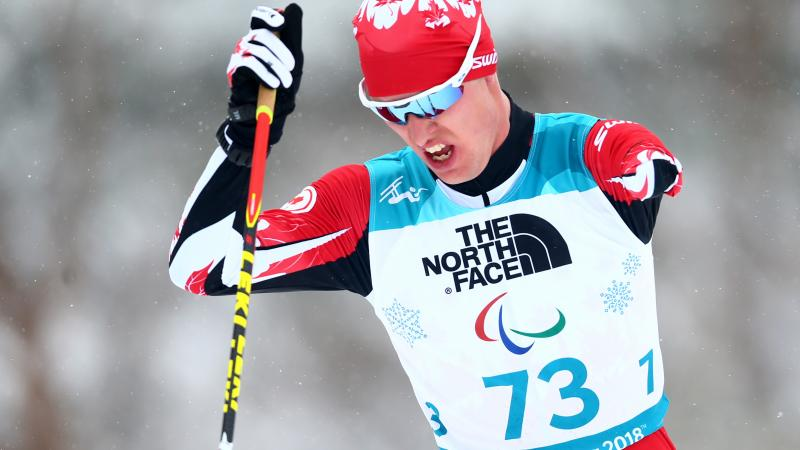 a male Para Nordic skier ploughs through the snow