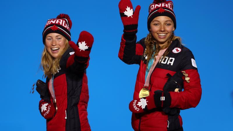 two female Nordic skiers wave from the podium