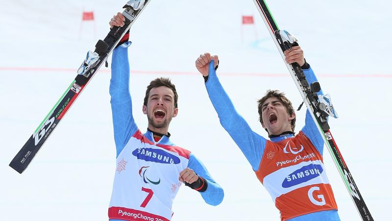a male vision impaired skier and his guide celebrate by holding up their skis