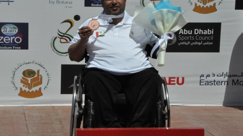 Man in wheelchair holding medal and flowers
