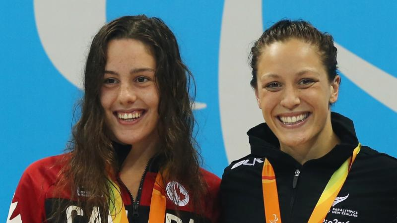 two female Para swimmers smiling on the podium