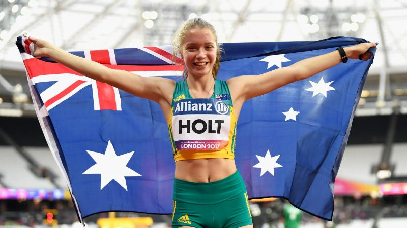 a female Para sprinter holding up the Australian flag