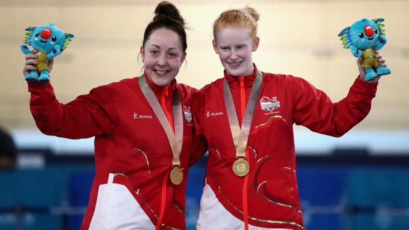 two female Para cyclists stand on the podium with their gold medals