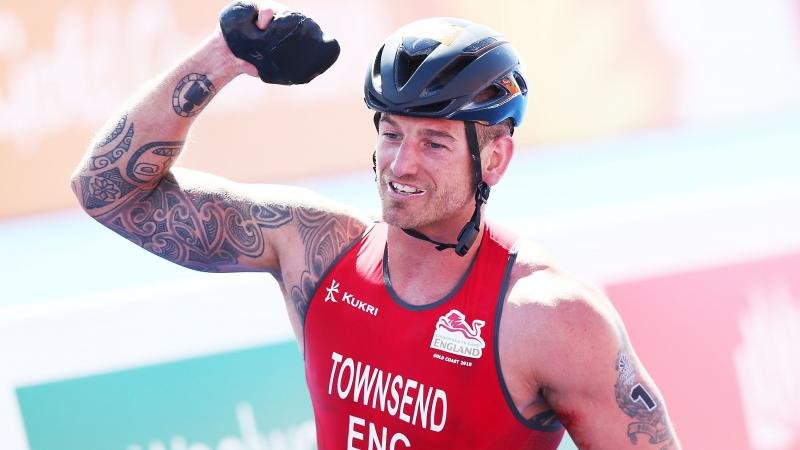 a male Para triathlete celebrates winning the race
