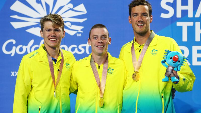 three male swimmers on the podium