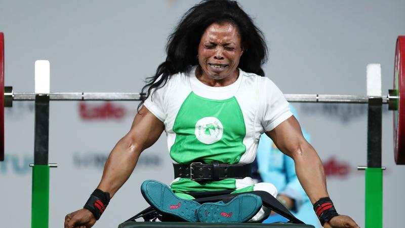 a female powerlifter celebrates on the bench