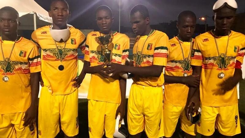 a group of blind footballers hold up a trophy