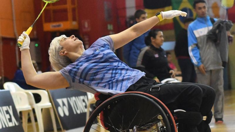 Woman in wheelchair playing badminton