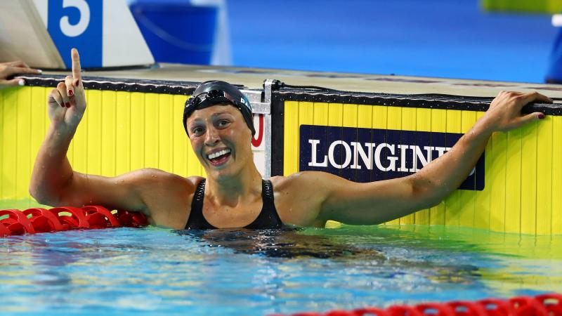 a female swimmer raises her arm in celebration in the pool