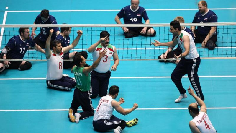 a group of male sitting volleyball players celebrate on the court