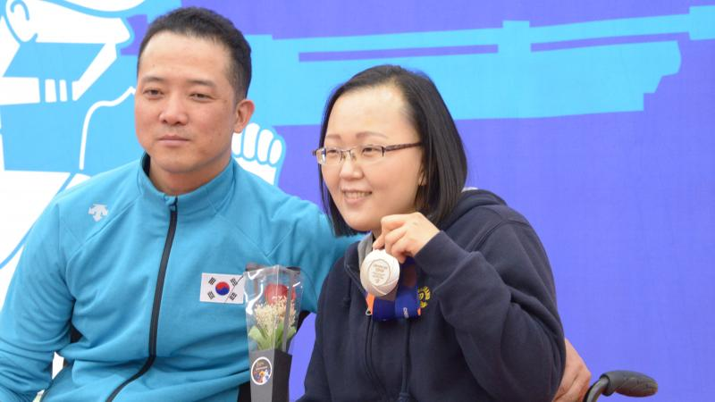 Man and woman in wheelchairs pose for photo with silver medal