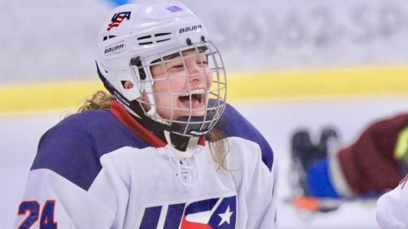 a female Para ice hockey player laughing on the ice