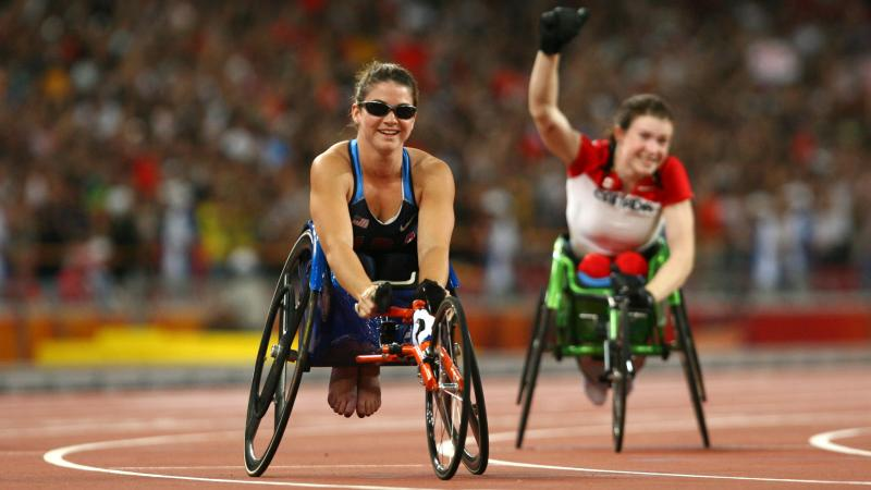 a female wheelchair racer celebrates after the finish line