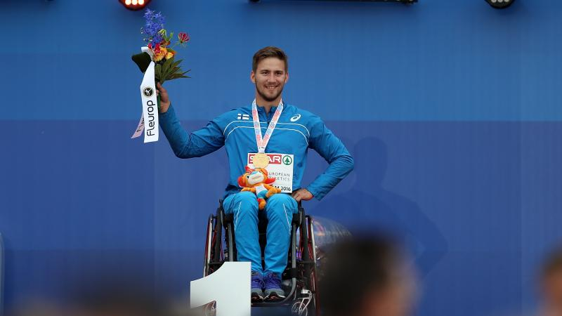 Person in a wheelchair on a podium holding flowers