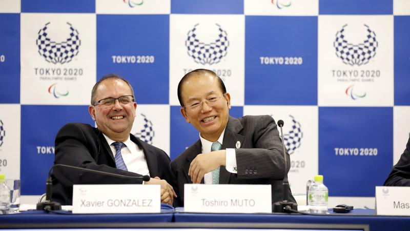 two men smiling and shaking hands