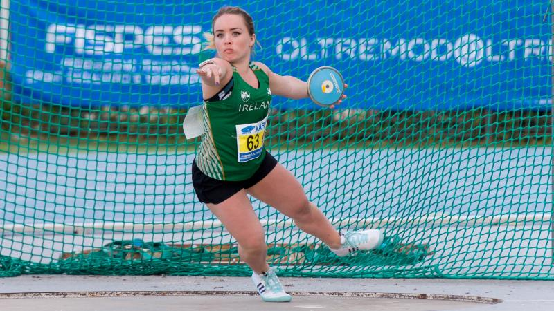 Short statured female discus thrower competing