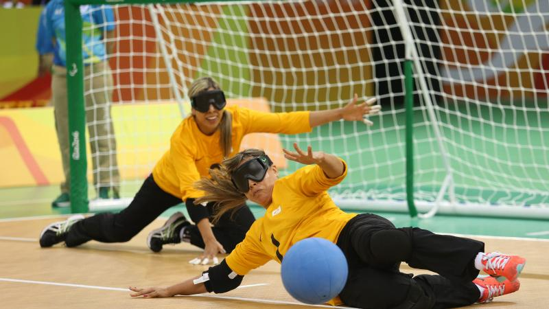 two female goalball players trying to stop a shot