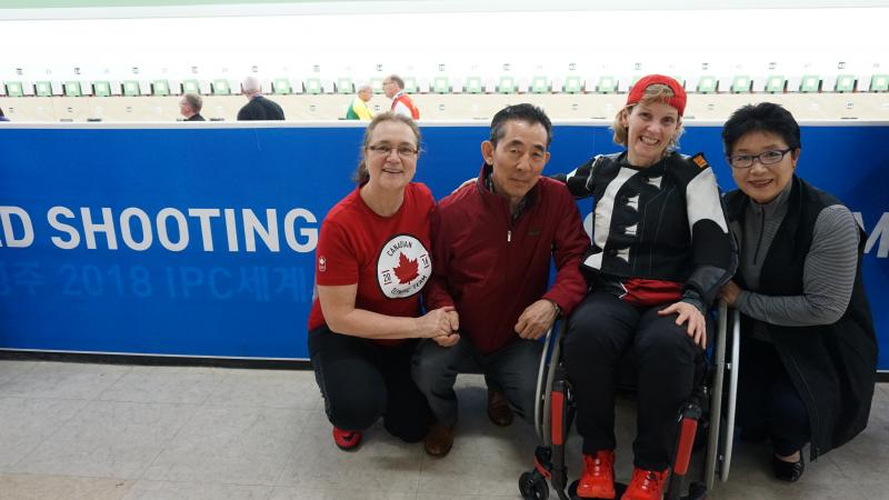a female Para shooter hugs and smiles with her former coach