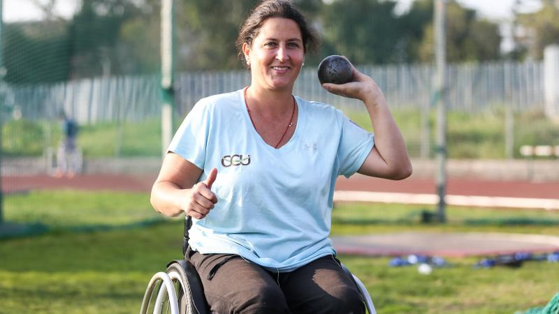 a female Para athlete prepares to throw a shot put