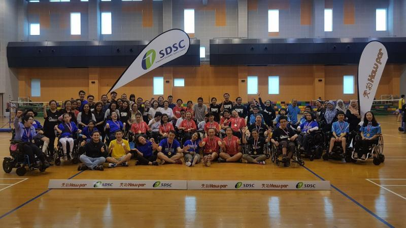 a group of boccia players and children sitting in a gym