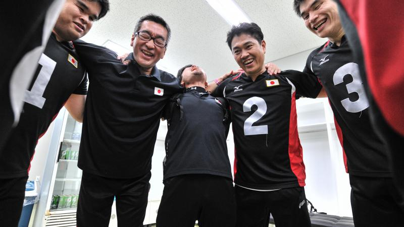 a group of male goalball players standing in a circle laughing