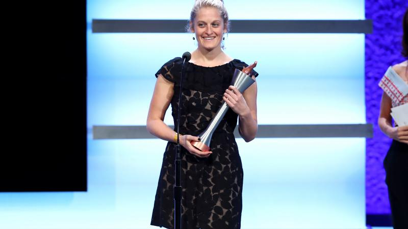 a woman stands on stage holding a trophy