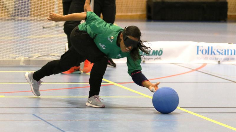 a female goalball player throws the ball