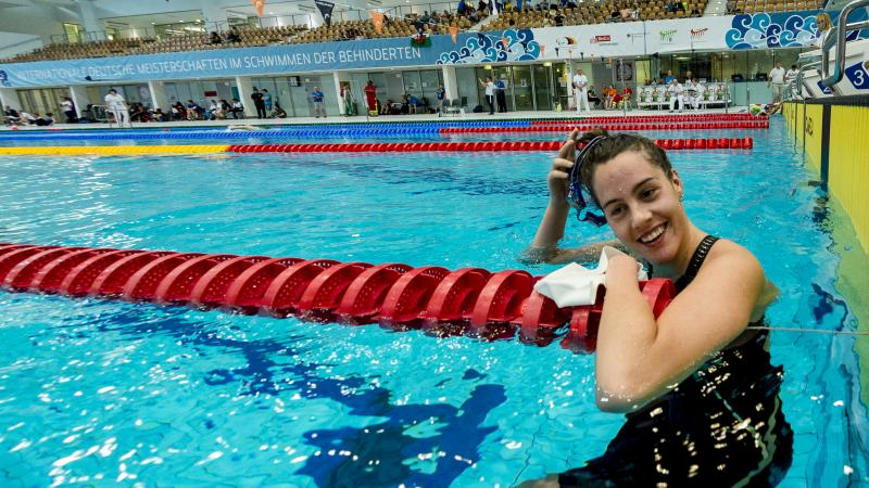 a female Para swimmer smiles in the water as she removes her swimming cap