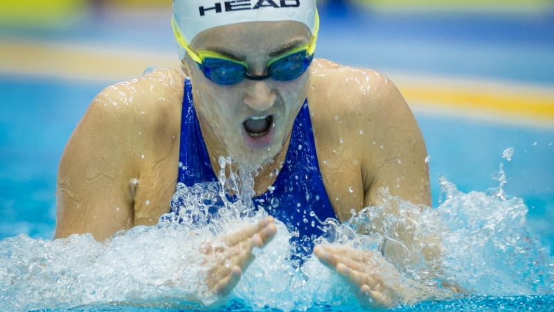 a female Para swimmer takes a breath during breaststroke