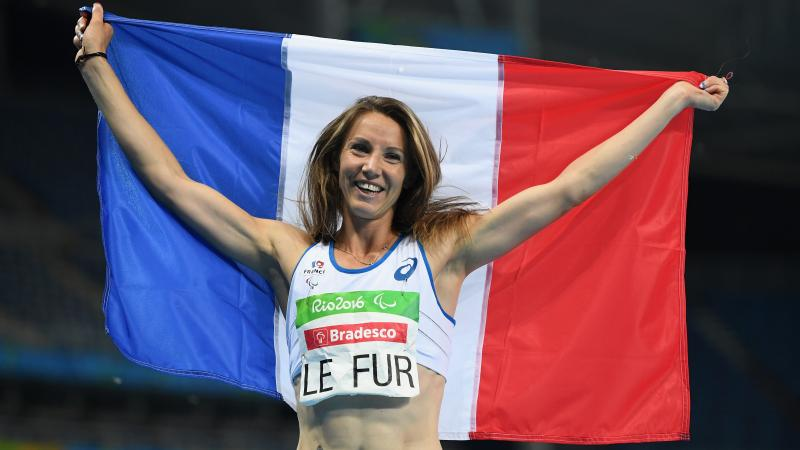 a female Para athlete holds up a French flag