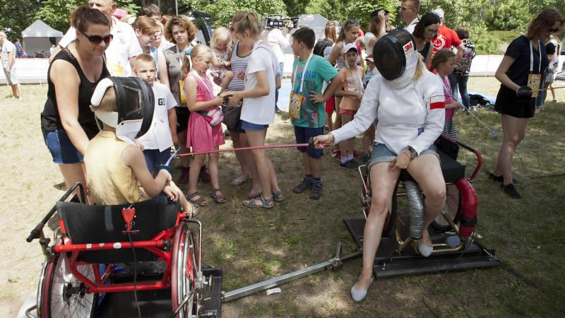 Group of children watching two people practicing wheelchair fencing