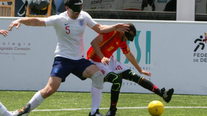 two male blind footballers battling for the ball