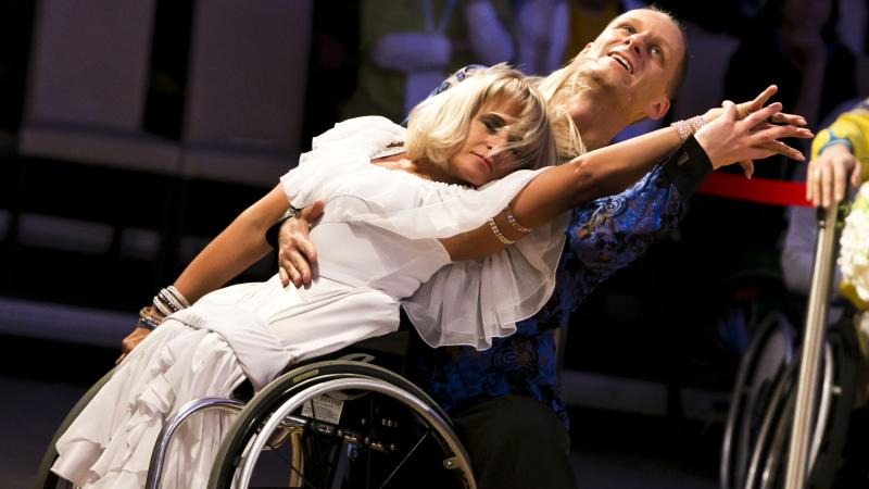 A female wheelchair dancer in a move with her able-bodied male partner