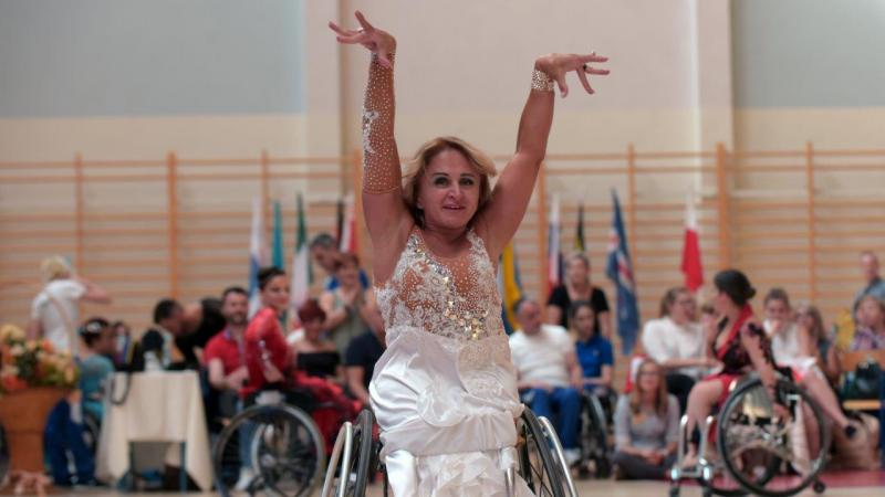 a female wheelchair dancer raises her arms above her head as part of a move
