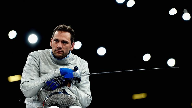 a male wheelchair fencer holding a foil and his helmet