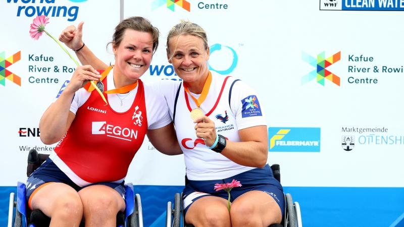 two female Para rowers in wheelchairs hug on the podium