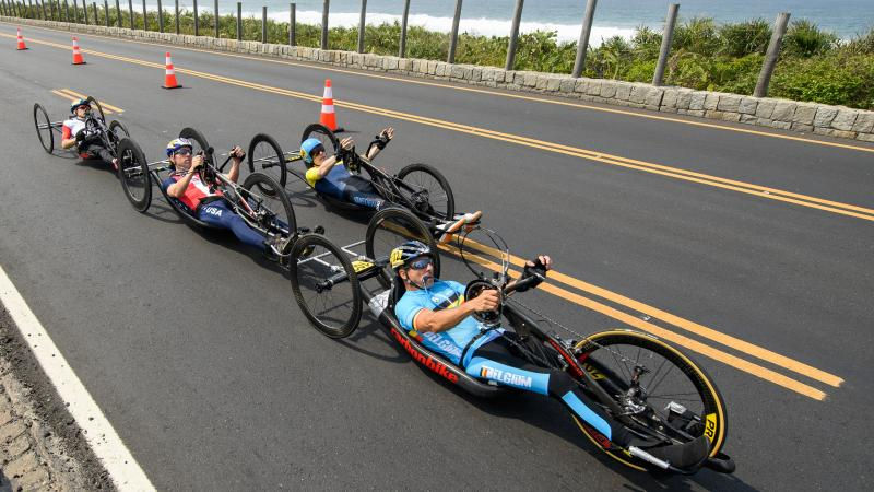 a group of male Para cyclists race along the road
