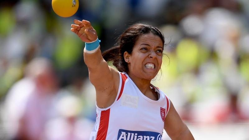 a female Para athlete of short stature throws a shot put