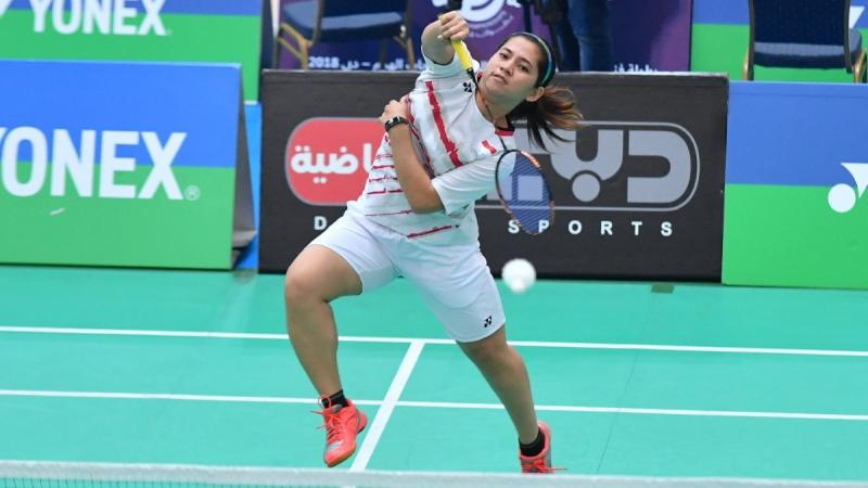 Female badminton player jumps to hit a birdie