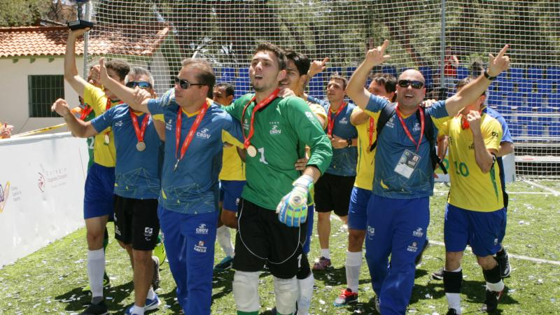 a group of male blind footballers celebrating on the football pitch